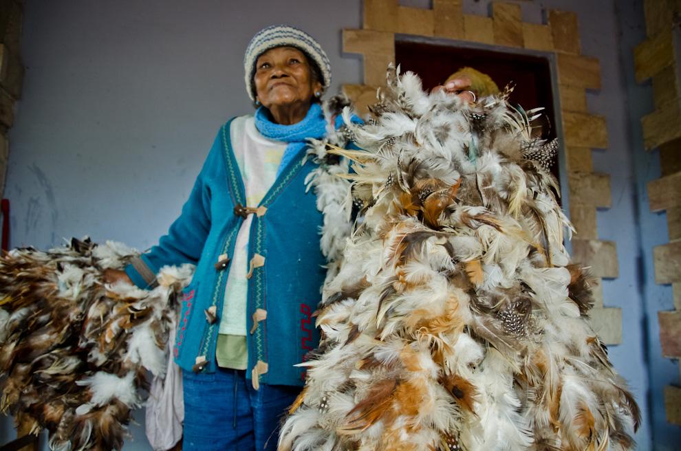 Ña Andresa, una promesera de 77 años, nos muestra su traje hecho de plumas de aves, que cada año utiliza para representar la cultura de los Guaicurúes en la época de celebraciones de la fiesta al Patrono San Francisco Solano, en Emboscada, departamento de Cordillera. (Elton Núñez).