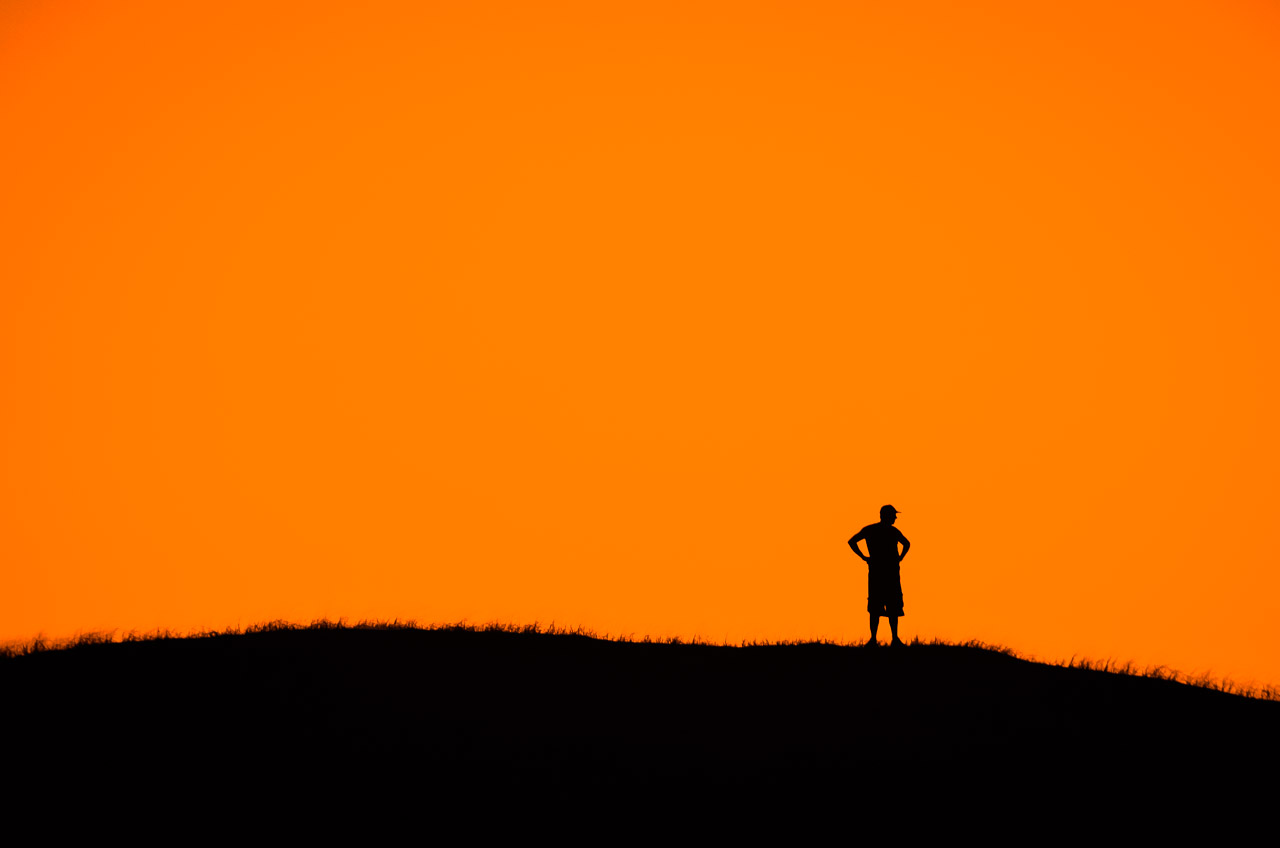Un turista observa el atardecer desde la cima de una duna en la Playa de la Viuda, en Punta del Diablo. (Elton Núñez)