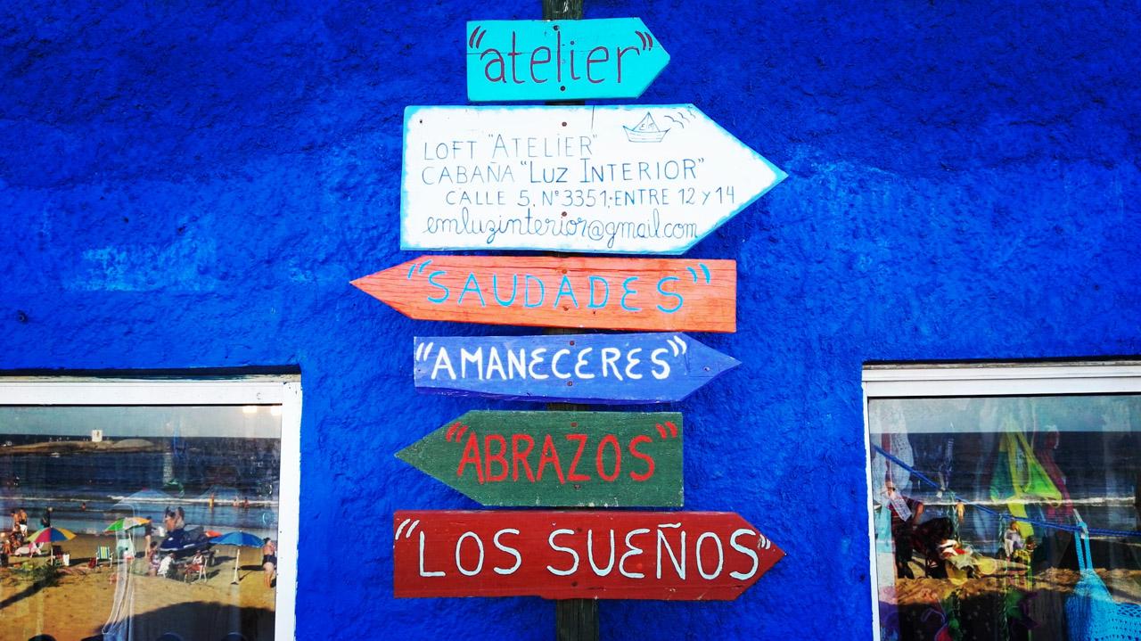 Un letrero señala las direcciones en donde se pueden encontrar algunas cabañas con nombres propios, en la Playa de los Pescadores, en Punta del Diablo. (Fotografía tomada con un smartphone Huawei P8, Elton Núñez)