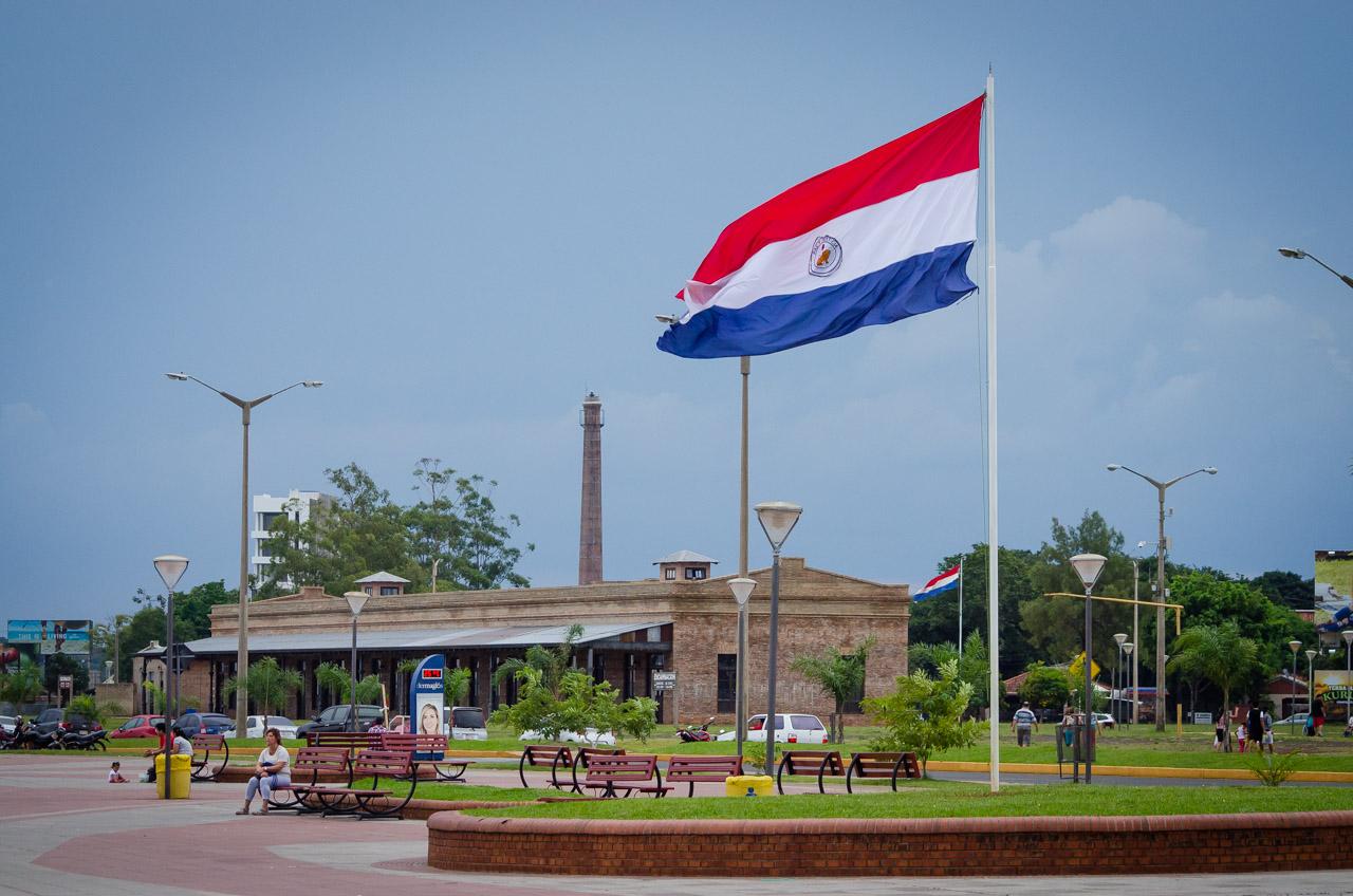 Una de las plazas de la costanera de Encarnación, ondea la bandera paraguaya frente a edificios históricos de Itapúa, como la réplica de la vieja estación de tren y la chimenea de la antigua aceitera de los años 40. (Elton Núñez)