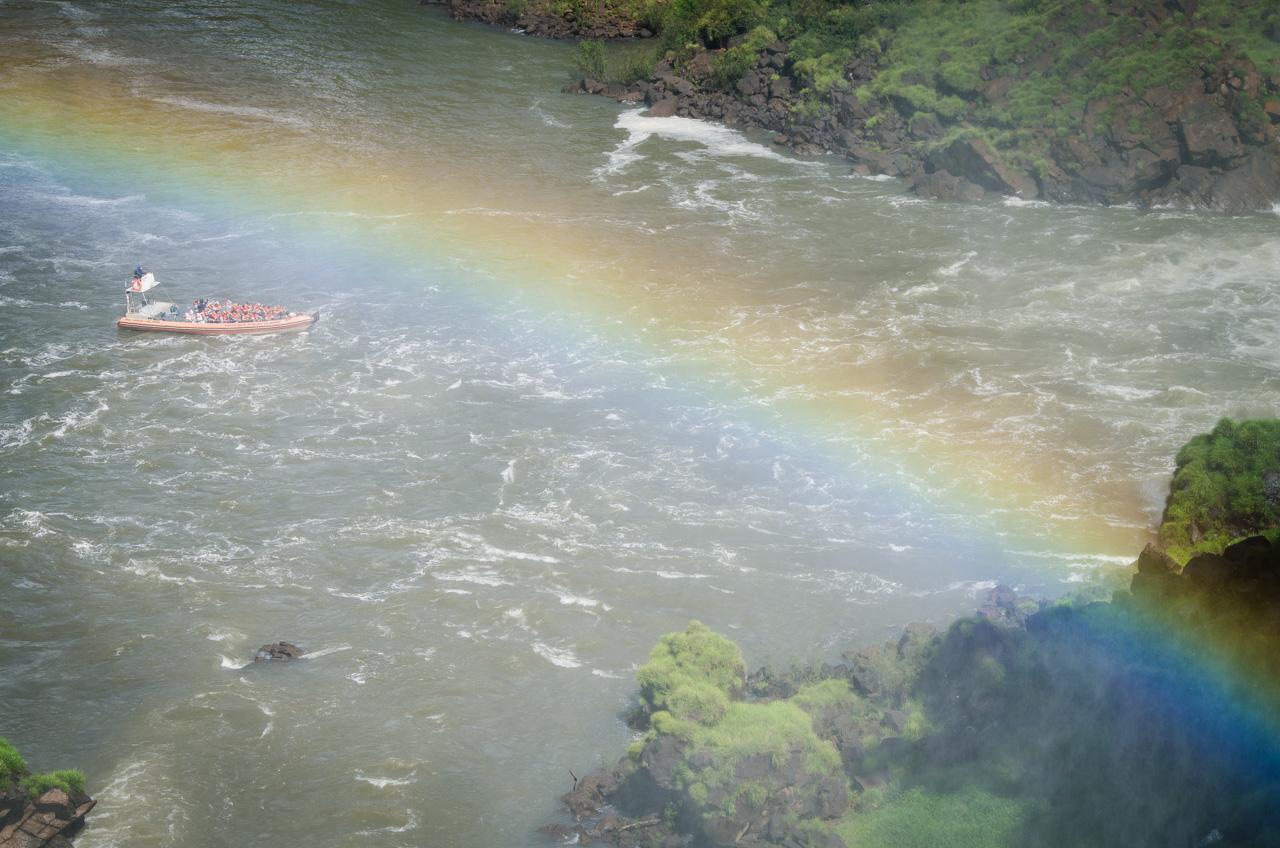 Un arcoíris se deja ver mientras turistas disfrutan de un tour en lancha por el río Iguazú, son llevados debajo mismo de los saltos de agua para que experimenten las aguas salvajes. (Elton Núñez).