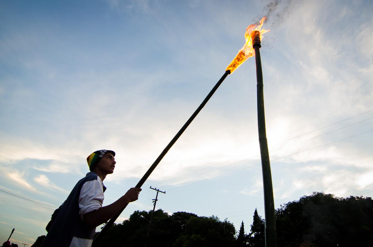Un joven voluntario de la organización de la procesión religiosa, enciende los candiles instalados a lo largo del Yvága Rapé en Tañarandy. Indicación de que el encuentro de los estacioneros con la Virgen Dolorosa está cerca. (Elton Núñez).
