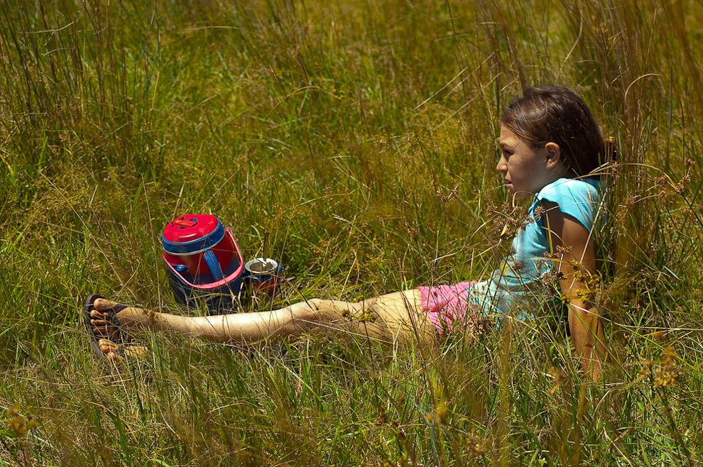 Niña reposando en los altos pastos de los campos de Caapucú, sirviendo tereré (bebida refrescante)  a su tía quien estaba trabajando en el lavado de ropas para luego tenderlas al aire. Campo de Caapucú, Departamento de Paraguarí. (Elton Núñez, 2009)