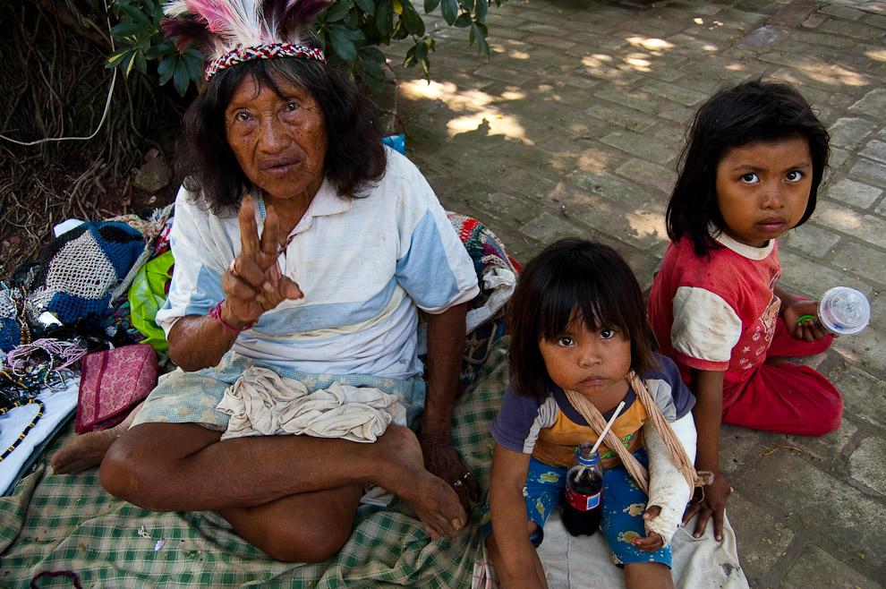 """Una madre Indígena Maká con sus dos hijos están vendiendo sus adornos y artesanías en el restaurante """"Las Palmeras"""", uno de los restaurantes más conocidos de Areguá (Areguá, Paraguay - Elton Núñez)"""