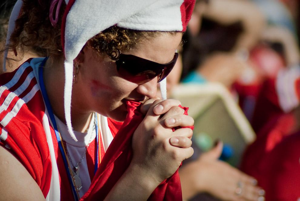 Una mujer hincha reza en los momentos cruciales del Partido de Futbol Paraguay vs España en la Plaza de la Democracia (Elton Núñez - Asunción, Paraguay)