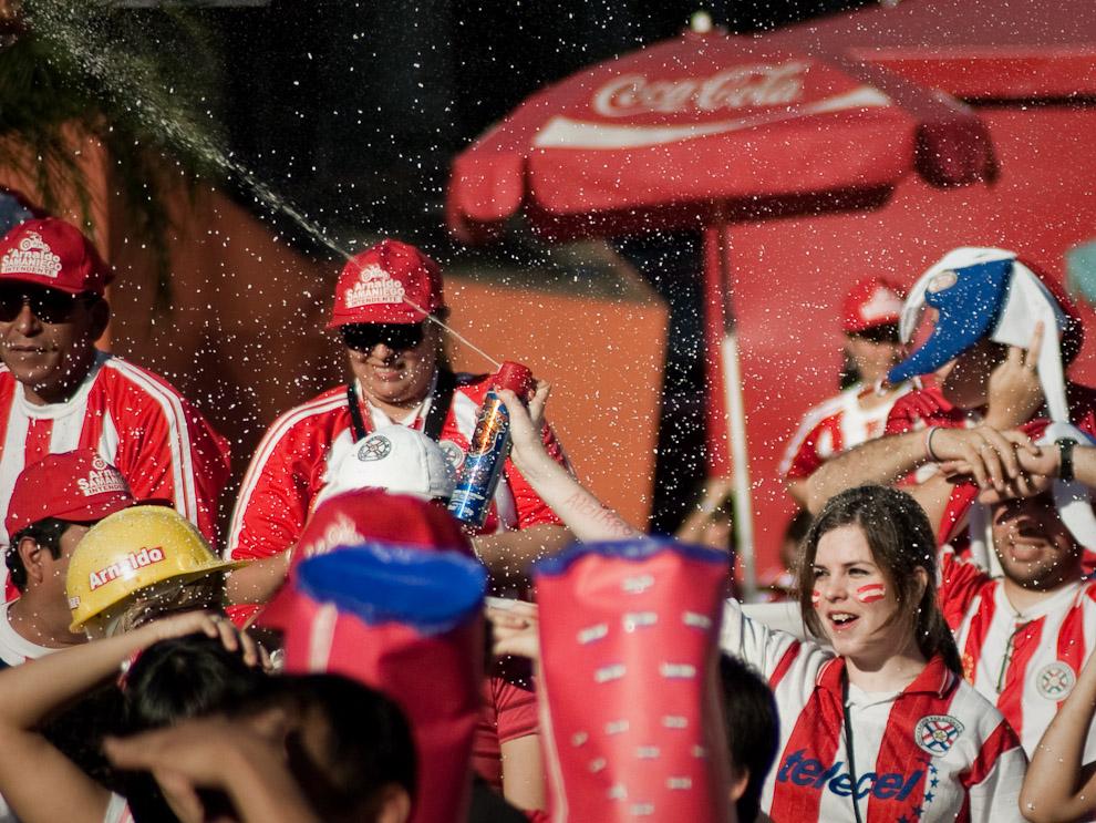 Una chica hace llover espuma sobre la gente reunida en la Plaza de la Democracia el dia que jugaron Paraguay vs España por la Copa Mundial Sudáfrica 2010 (Elton Núñez - Asunción, Paraguay)
