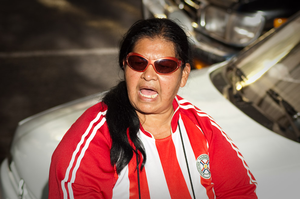 Una mujer vendedora de comestibles viste la remera albirroja frente a la Plaza de la Democracia durante el partido de Paraguay vs España (Elton Núñez - Asunción, Paraguay)