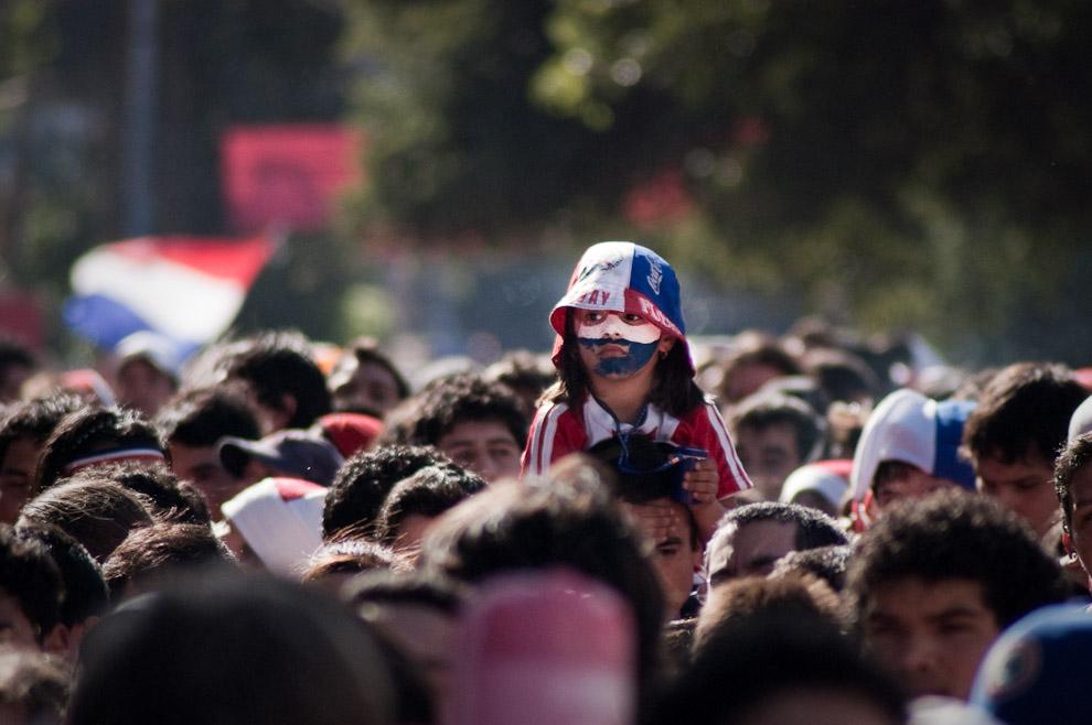 Una niña con la cara pintada con los colores de la bandera Paraguaya espera con su padre el momento de la apertura de las puertas hacia las Plateas en el Estadio Defensores del Chaco (Elton Núñez - Asunción, Paraguay)
