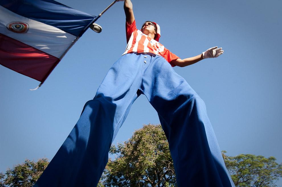 Un acróbata de circo viste los colores de la bandera Paraguaya alentando al equipo sobre la calle Palma (Elton Núñez - Asunción, Paraguay)