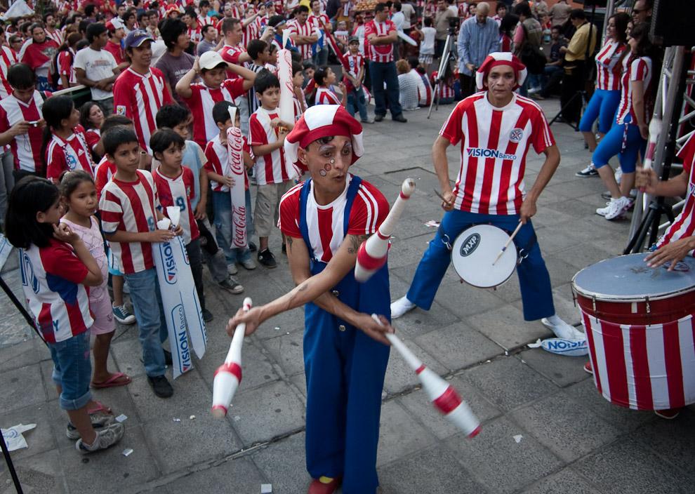 Un acróbata de circo entretiene a los chicos durante el descanso del primer tiempo en el partido transmitido por televisión de Paraguay vs España (Elton Núñez - Asunción, Paraguay)