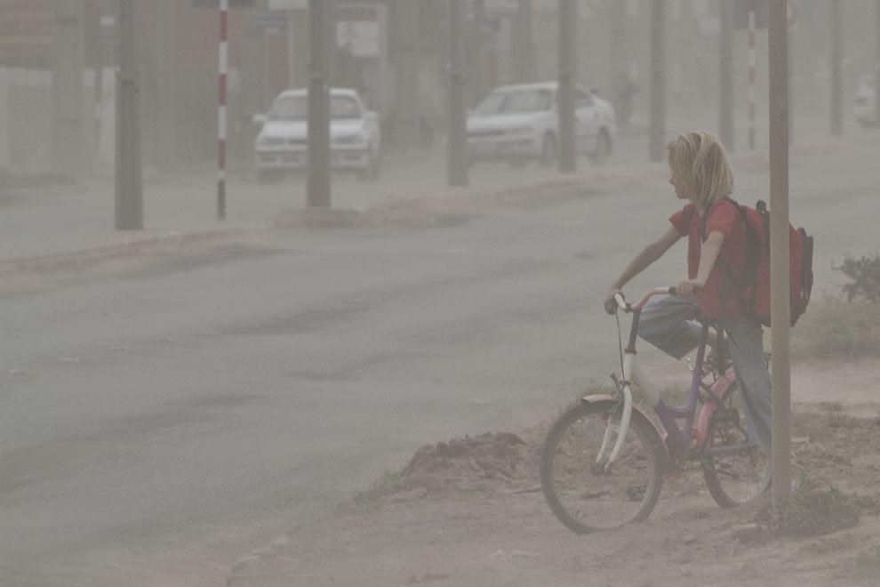 Una niña vuelve del colegio e intenta cruzar las calles en medio de una tormenta de polvo en la Ciudad de Loma Plata (Tetsu Espósito - Loma Plata, Chaco, Paraguay)
