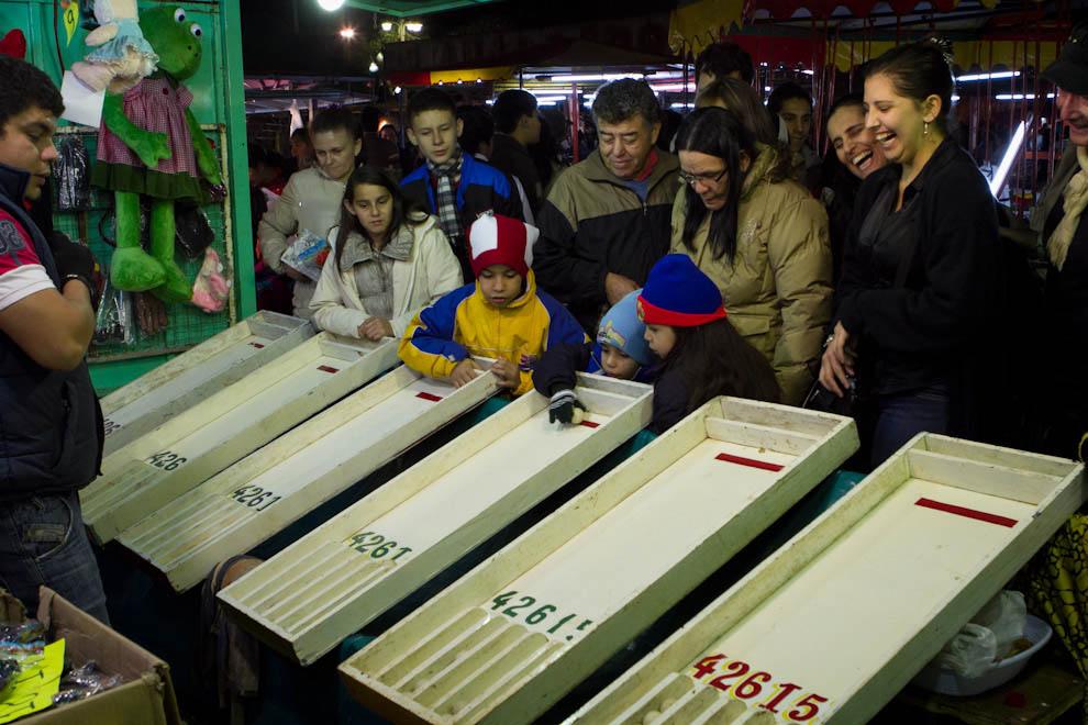 Niños y adultos se divierten probando su suerte en uno de los tantos juegos . (Tetsu Espósito - Mariano Roque Alonso, Paraguay)