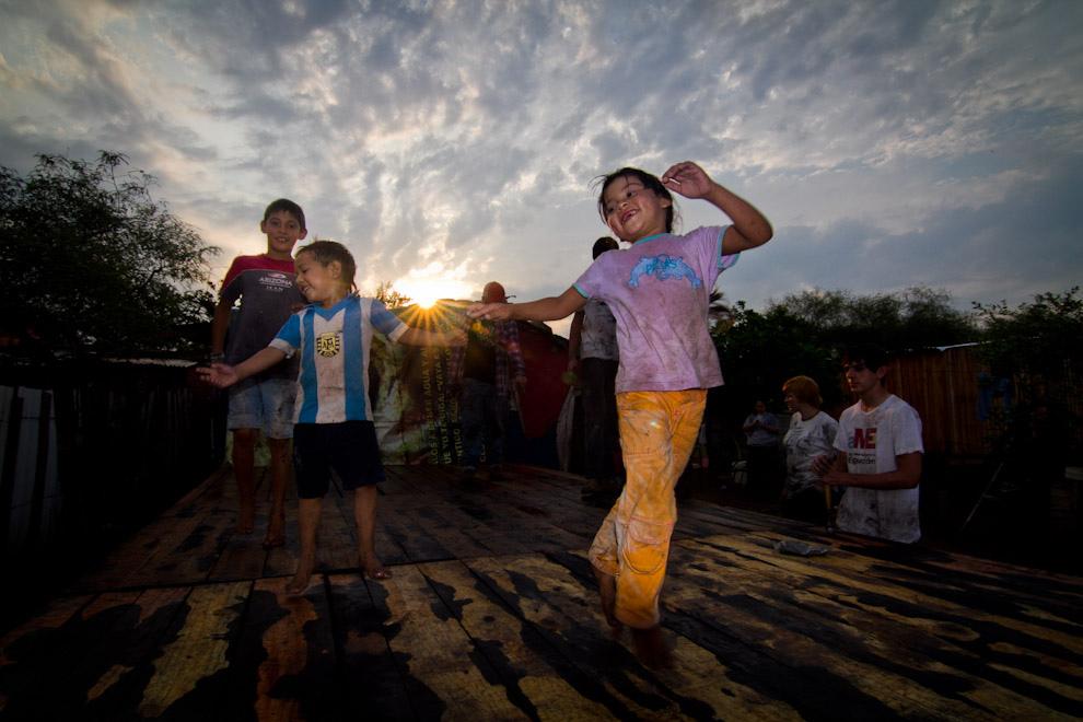 Los niños juegan sobre el piso recién instalado en las últimas horas de la tarde del sábado. (Tetsu Espósito - Lambaré, Paraguay)