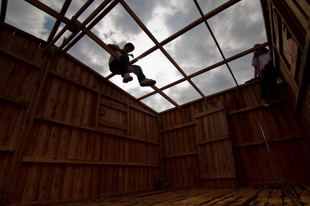 Dando los toques finales en las vigas del techo de la vivienda. (Tetsu Espósito - Lambaré, Paraguay)