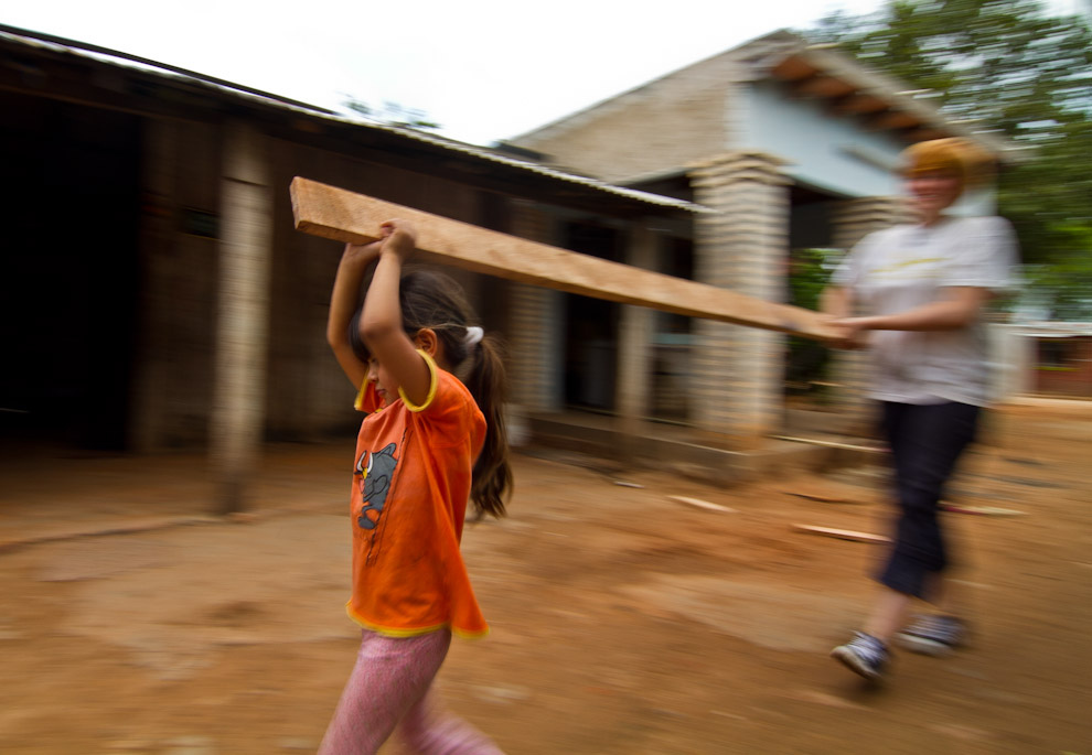 Una niña ayuda a una voluntaria a trasladar un listón que servirá de viga para el techo de la vivienda. (Tetsu Espósito - Lambaré, Paraguay)