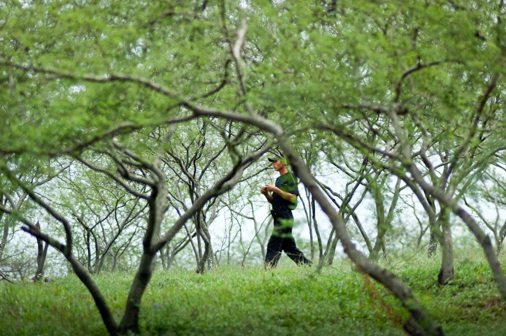 """Un guardia de seguridad recorre el parque ecologico """"Cateura"""", una zona verde y bien cuidada al lado mismo del basural de Cateura, este lugar demuestra que el terreno es fértil y sustentable para espacios verdes. (Elton Núñez - Asunción, Paraguay)"""