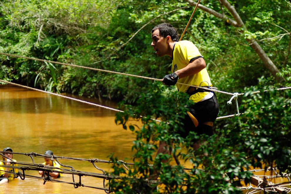 Un participante de la categoría Trekking 10km llega a la etapa final, que consiste en cruzar un último arroyo mediante ejercicios de cuerda y puente mono, mientras es observado por otros participantes que ya concluyeron la carrera. (Elton Núñez - Piribebuy, Paraguay)