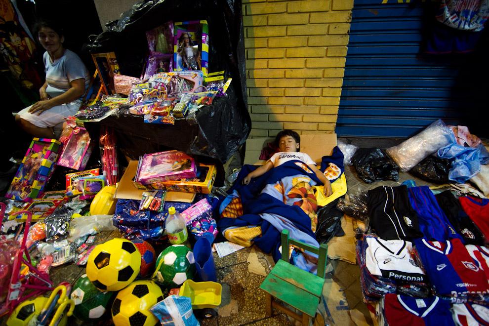 En las primeras horas de la madrugada del 6 de Enero, un niño duerme en la vereda, en medio de los juguetes para la venta, sobre la Avenida E. Ayala. (Tetsu Espósito - Asunción, Paraguay)