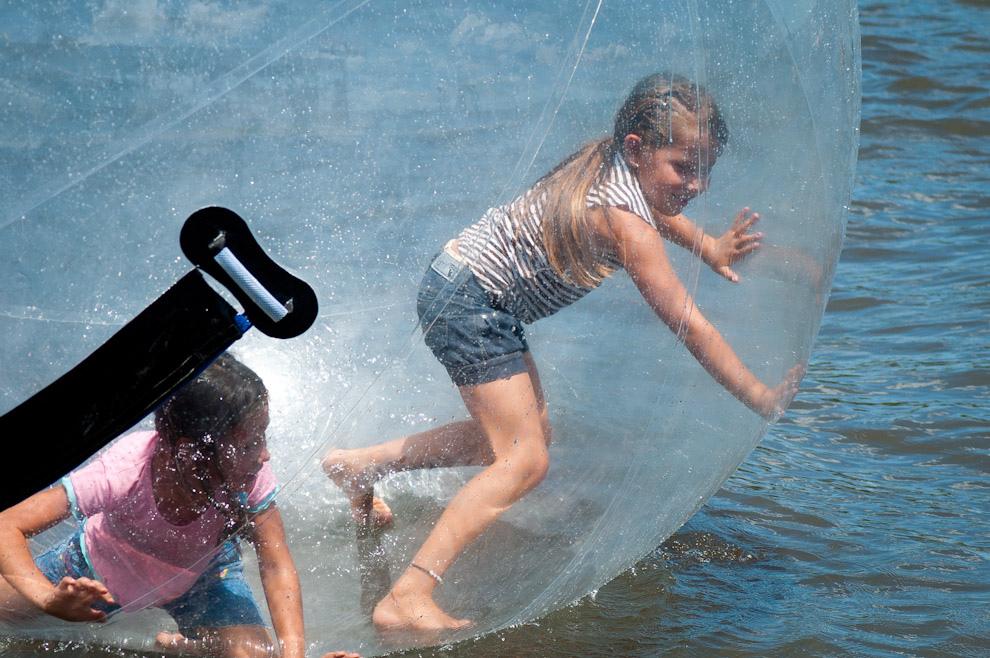 Dos niñas se divierten dentro de una burbuja inflada sobre las aguas del Lago Ypacaraí, esta burbuja de plástico grueso se infla con un equipo especial estando la persona ya adentro, es un servicio que se renta por unos minutos de total diversión. (Elton Núñez - Ypacaraí, Paraguay)