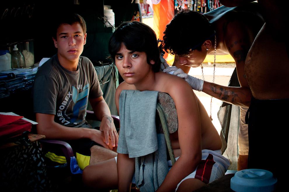 Un muchacho se hace un tatuaje mientras el amigo espera su turno, el domingo 23 de Enero pasado, en una de las tiendas de colocación de tatuajes en la plaza de la Ciudad cerca de la Iglesia de San Bernardino. (Elton Núñez - Ypacaraí, Paraguay)