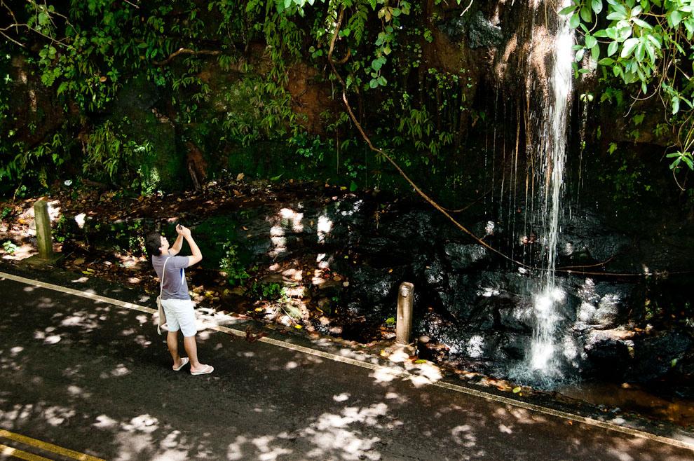Un muchacho se queda en la ruta que pasa por Mbatoví para fotografiar una bonita cascada de las tantas que hay en esa zona, la llamativa cascada hace que la gente dé una pausa a su viaje para refrescarse con sus aguas o sacar una foto. Esta ruta que pasa por Mbatoví es la que une Paraguarí con Ruta 2 atravesando Piribebuy. (Elton Núñez - Piribebuy, Paraguay)