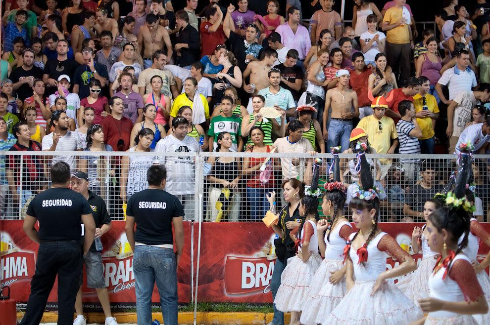El público disfruta del desfile de las niñas del Club Universal vestidas con ropas de Aó Po'í y lo que sería las botellas sobre sus cabezas como parte de la alegoría del Bicentenario del Paraguay, el viernes 18 de Febrero pasado. Los guardias de seguridad no faltaron esa noche garantizando el orden durante todo el evento. (Elton Núñez - Encarnación, Paraguay)