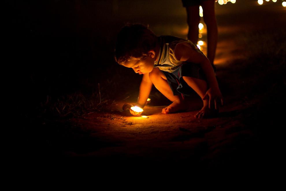 Un niño pequeño, apaga las velas que alumbran el camino, horas después de finalizada al procesión de Tañarandy. (Tetsu Espósito - San Ignacio, Paraguay)