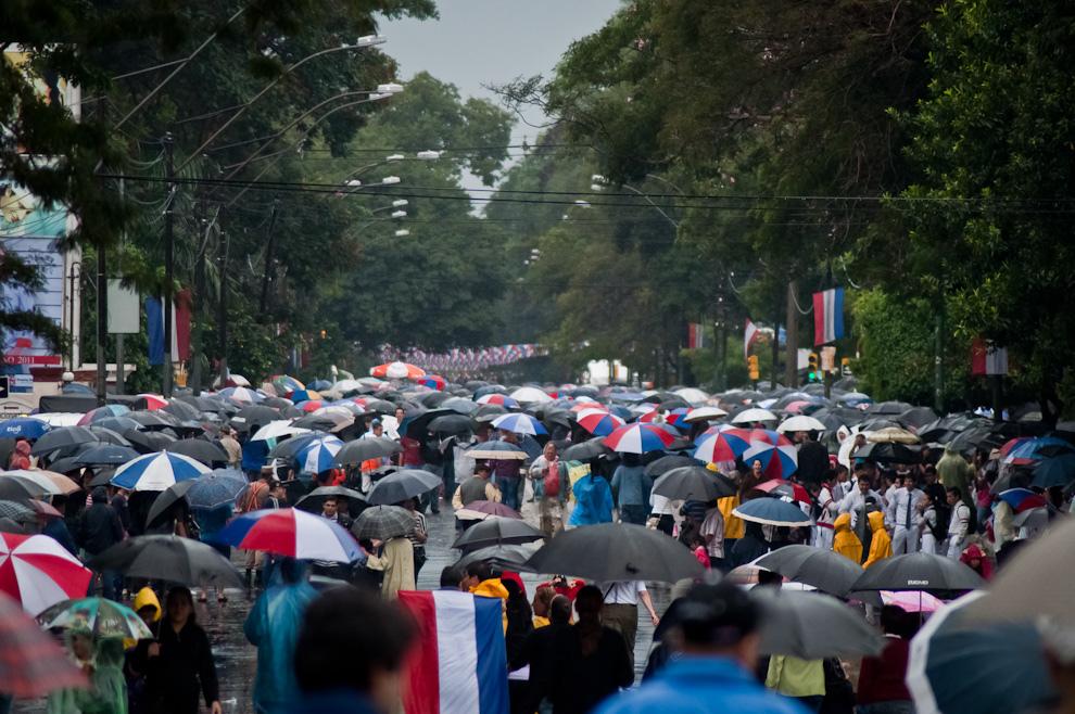 Pese a la intensa lluvia que se registraba en Asunción, mucha gente entre ellos grupos de jóvenes y familias se encuentran aguardando para participar, celebrar y ver el desfile de los Militares sobre la avenida Mariscal López. La fiesta se vivió aún bajo los paraguas. (Elton Núñez - Asunción, Paraguay)