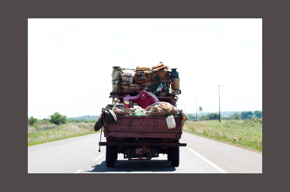 Un pasajero duerme mientras es llevado en la carrocería de un vehículo de carga teniendo que soportar el fuerte sol durante todo el viaje desde San Pedro hasta Asunción por la nueva ruta 3, el pasado 19 de diciembre de 2010. Entre la cantidad de mercaderías y distintos objetos el pasajero encontró su espacio para acomodarse. (Elton Núñez)