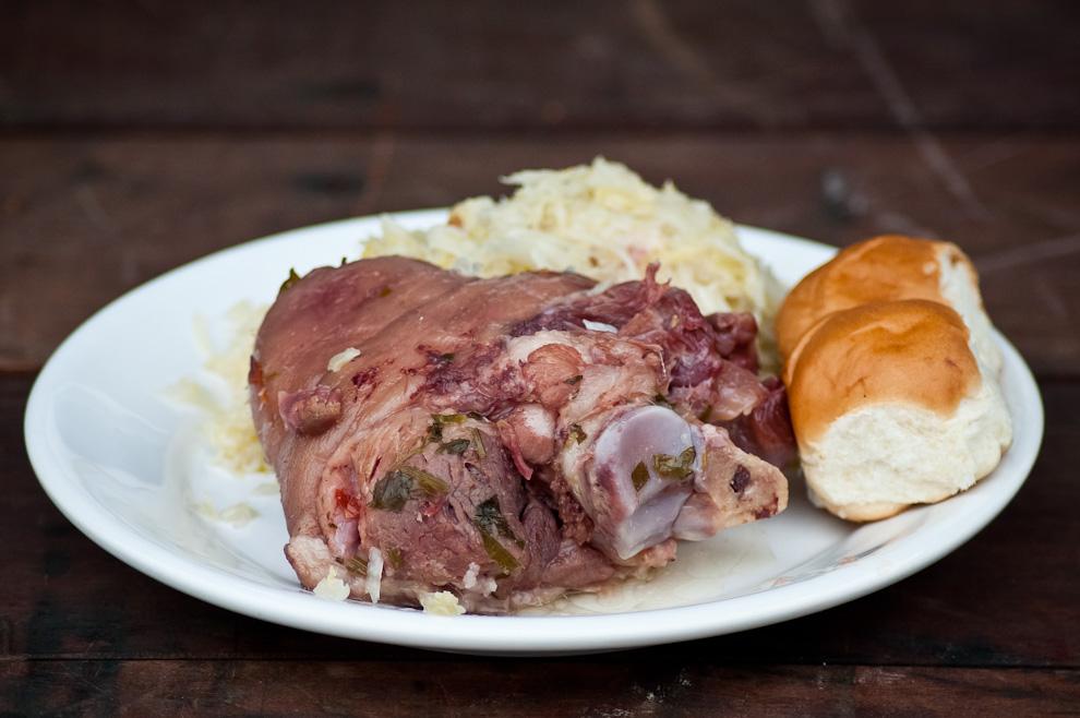 """Una toma cercana del clásico Eisbein, (codillo de cerdo), es un pedazo de la pata trasera o delantera del cerdo que se cocina por varias horas en un caldo condimentado, se sirve con """"chucrut"""", un acompañamiento a base de repollo fermentado en agua salada, un plato delicioso que se consume masivamente en estas clases de fiestas. (Elton Núñez)"""