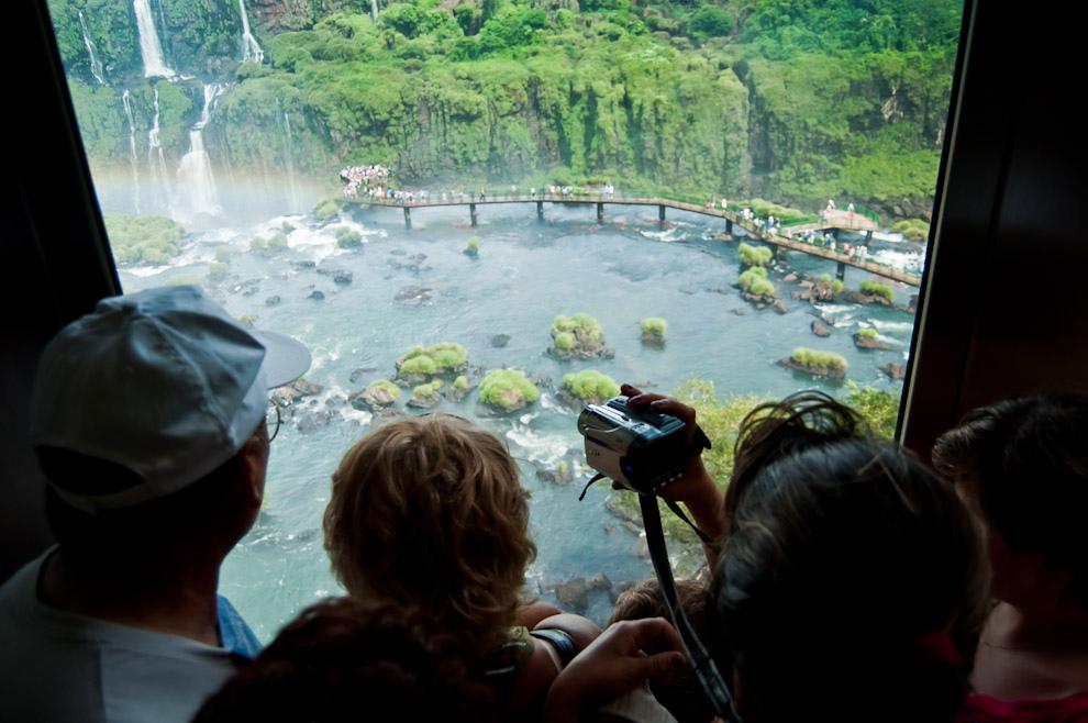 Turistas argentinos contemplan las cataratas de Iguazú desde la ventana de un ascensor, tomando fotografías y grabando en video todo el recorrido que implica la visita a esta considerada maravilla del mundo. (Elton Núñez)