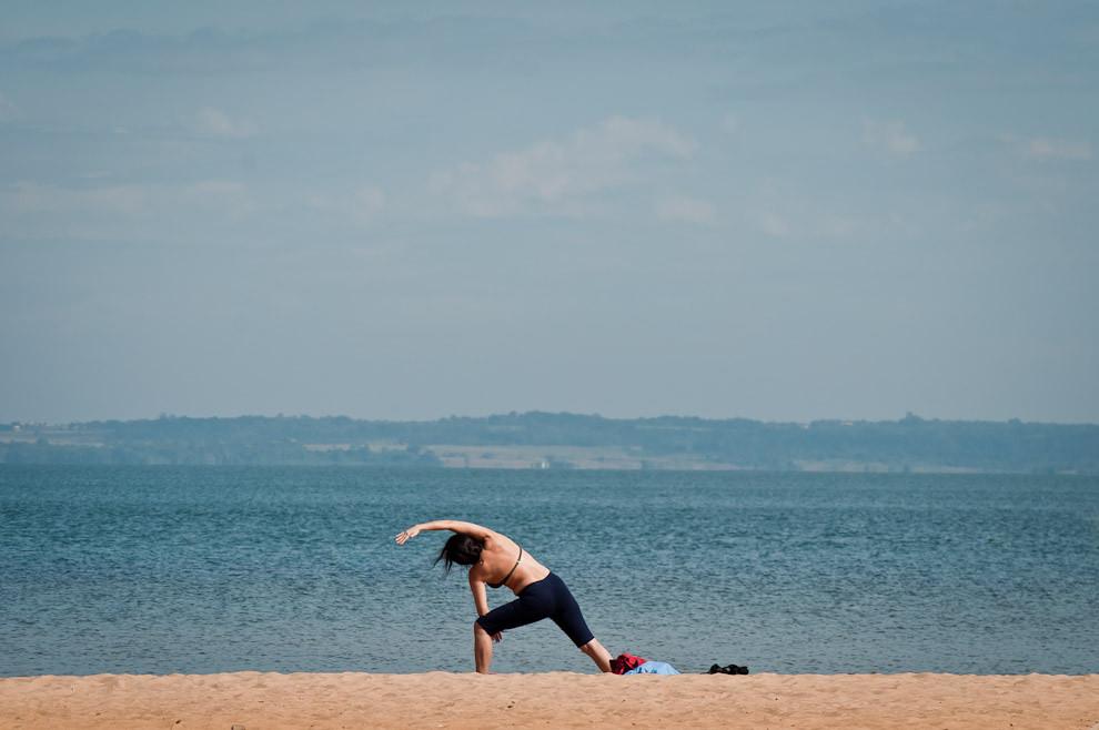 """Una mujer hace estiramientos en la nueva playa """"San José"""" de la costanera de Encarnación el miércoles 4 de Abril en horas tempranas de la mañana, a medida que avanzaba el día los turistas se acercaban al lugar para instalarse y disfrutar de un día agradable.  (Elton Núñez)"""