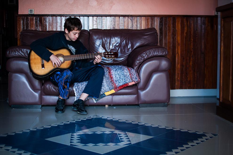 Un niño practica la ejecución de su guitarra durante la siesta mientras descansaba luego de toda una mañana de prácticas musicales el día del megaconcierto en la ciudad de Caacupé. (Elton Núñez)