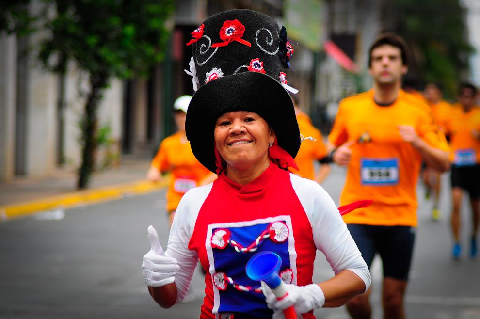 Una participante de la carrera vestida totalmente con los colores de la Albirroja corre con los demas competidores soplando su vuvuzela y animando al pùblico. (Elton Núñez)