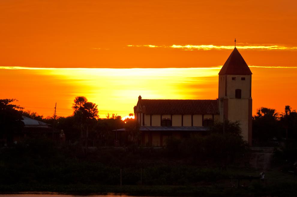 """Durante un rojo atardecer, el sol se ocultaba detrás de una iglesia en la zona cercana a """"Porto Murtinho"""" durante nuestro regreso aguas abajo rumbo a Concepción. (Elton Núñez)"""