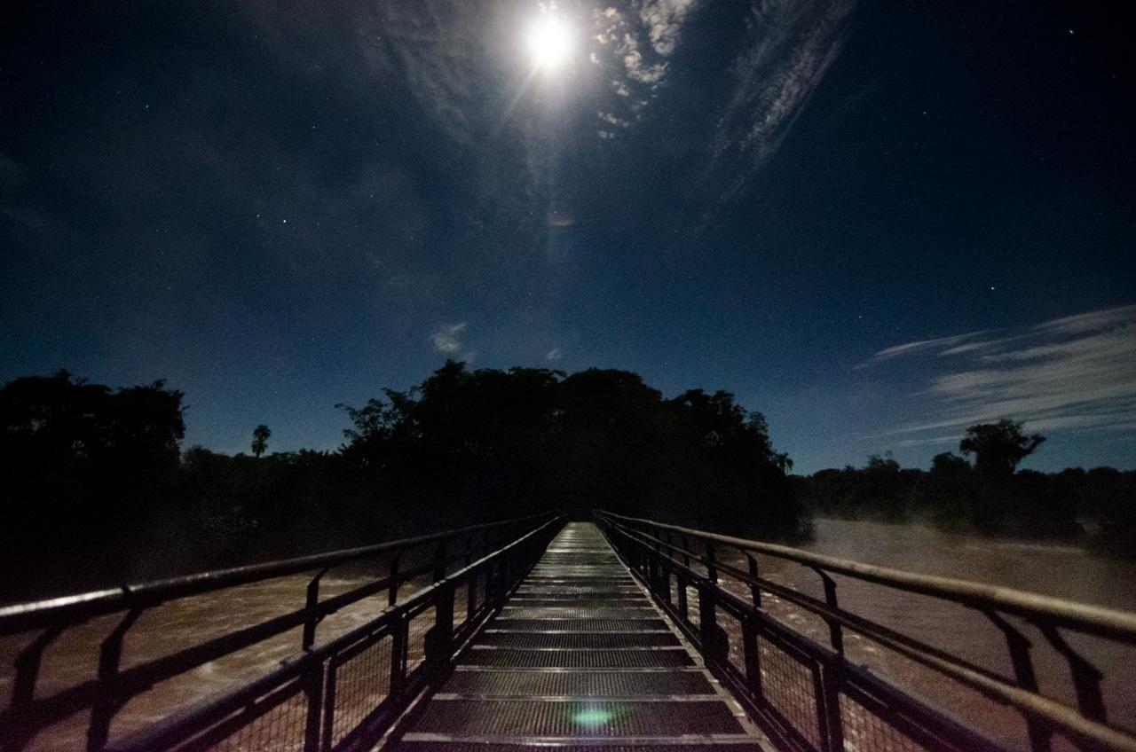 La luz de la luna ilumina el sendero que conduce hasta las Cataratas del Iguazú, del lado argentino, la gran precipitación de agua de Garganta del Diablo rocía el ambiente manteniendo siempre húmedo el circuito. (Elton Núñez).